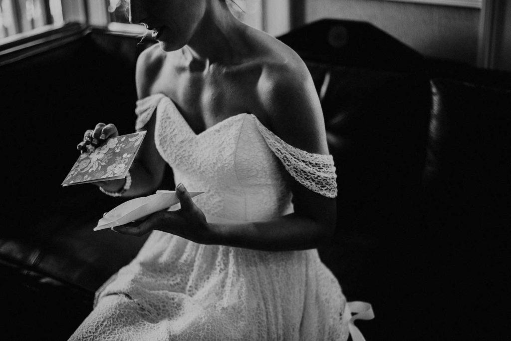 bride reads wedding card in her wedding dress