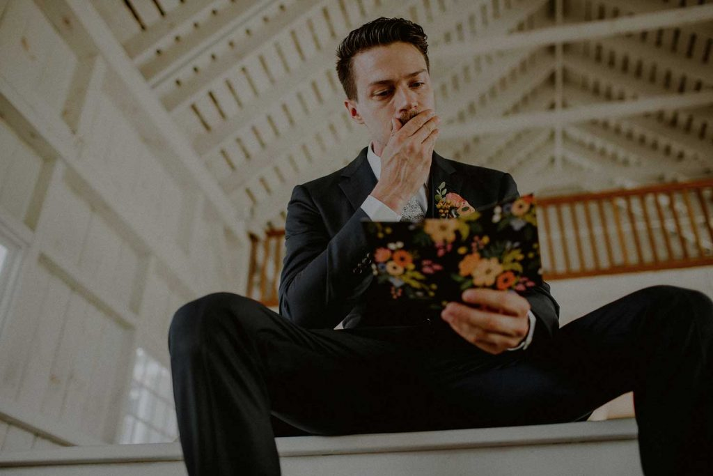emotional groom while reading card from bride