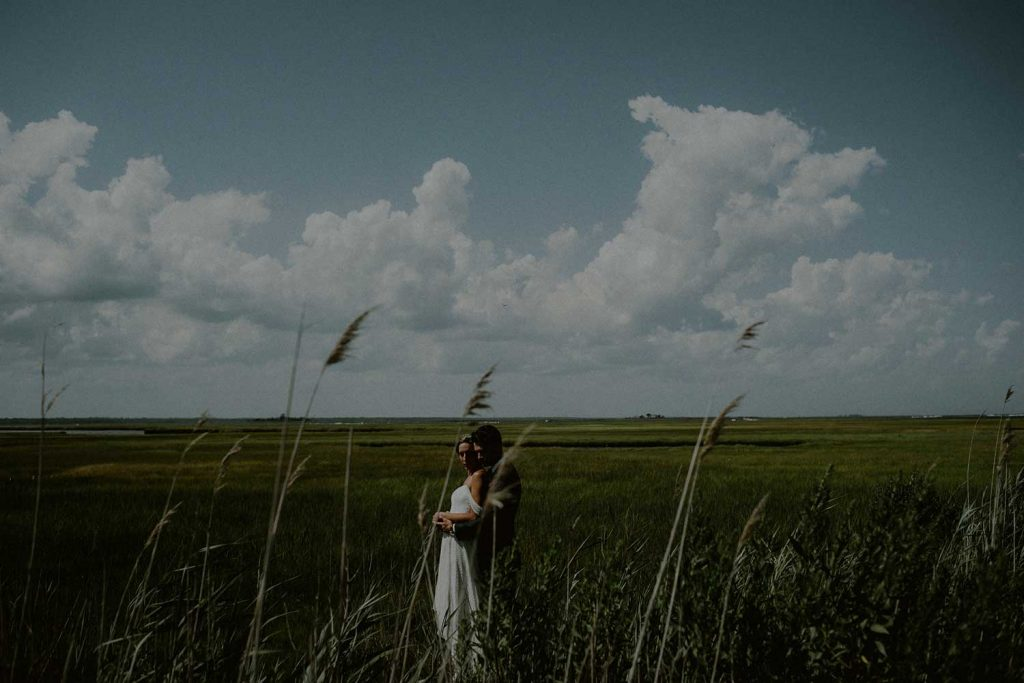 portrait of bride and groom in marsh with clear summer sky
