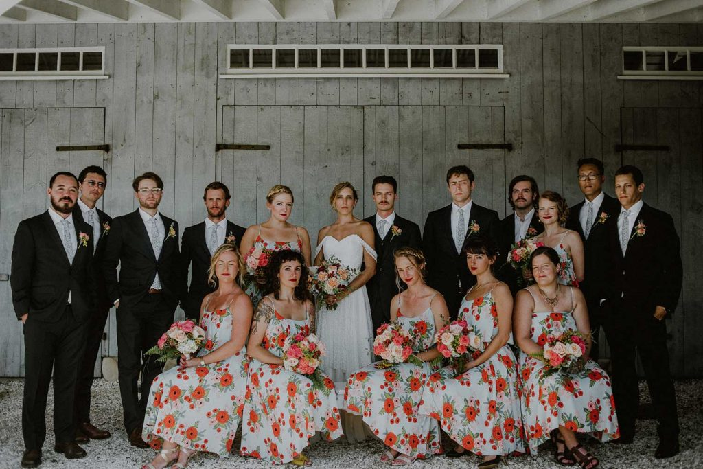 bridal party portrait in front of barn at bonnet island with coordinating floral bridesmaids dresses
