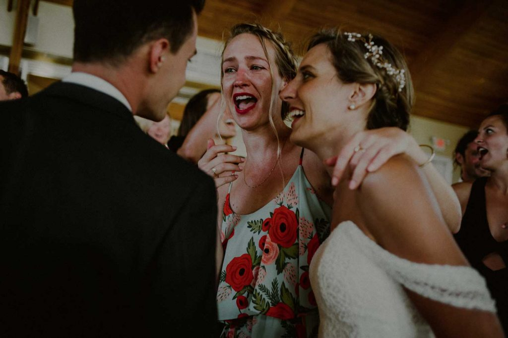 bride and groom laugh with guests at their reception