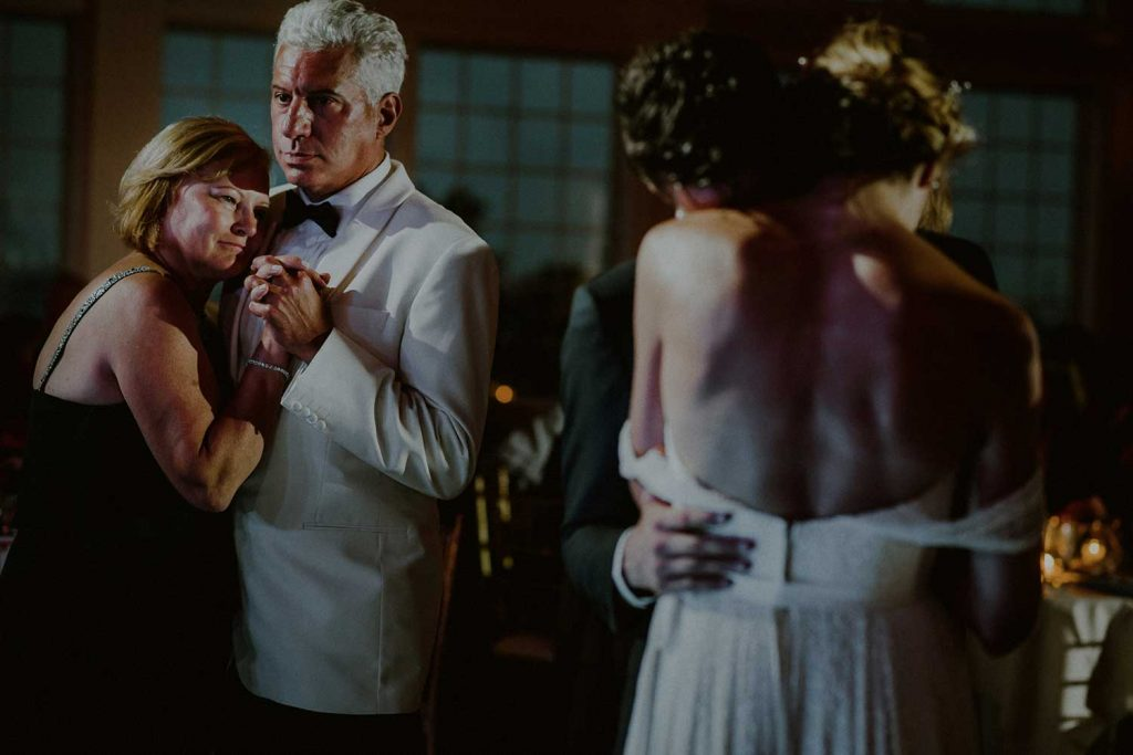 intimate wedding reception moment of couple dancing next to parents