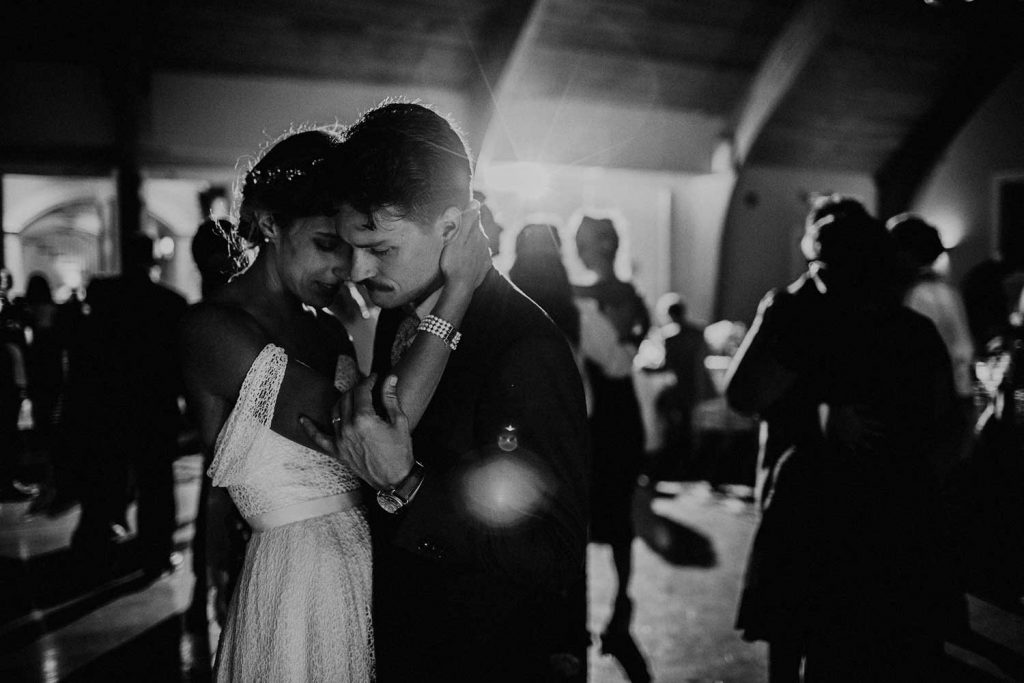 candid wedding photo of bride and groom dancing at reception