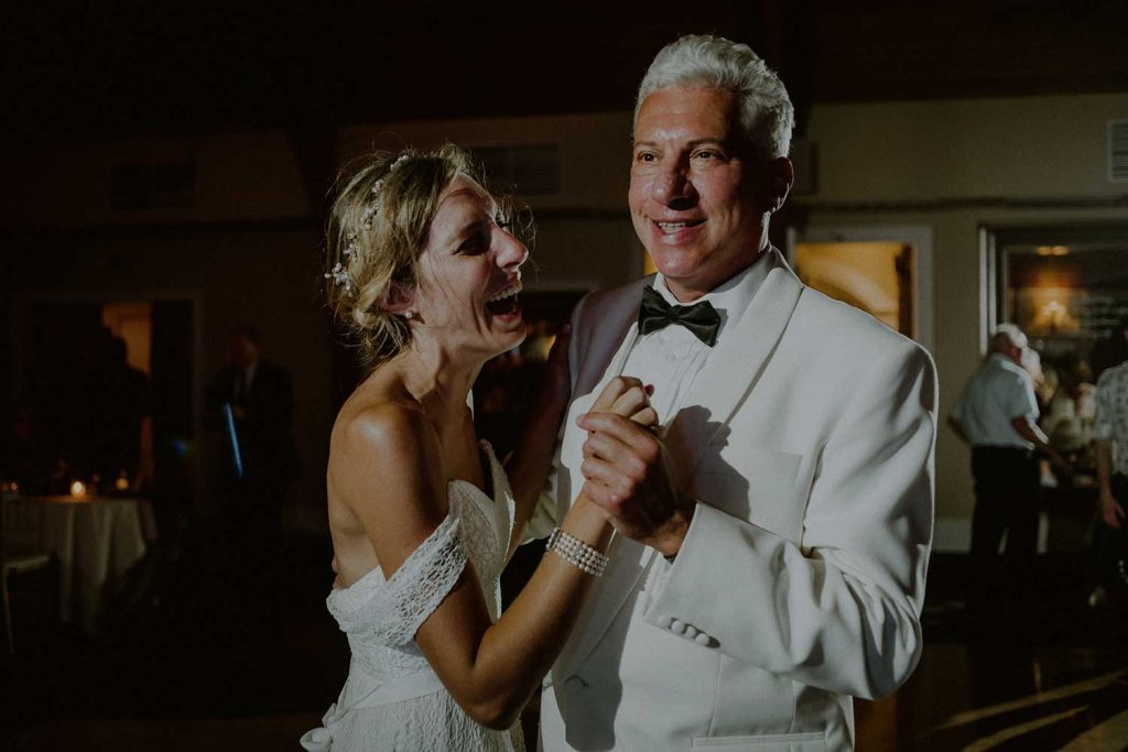 bride and father dance and laugh during wedding reception