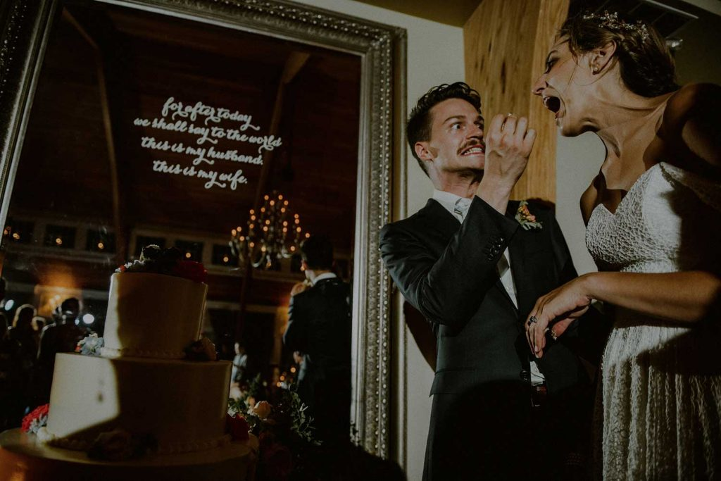 silly moment between bride and groom cutting cake at wedding reception