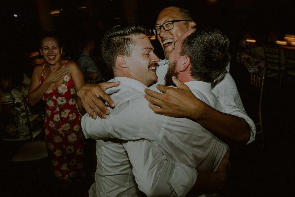 groom dancing with friends at wedding reception